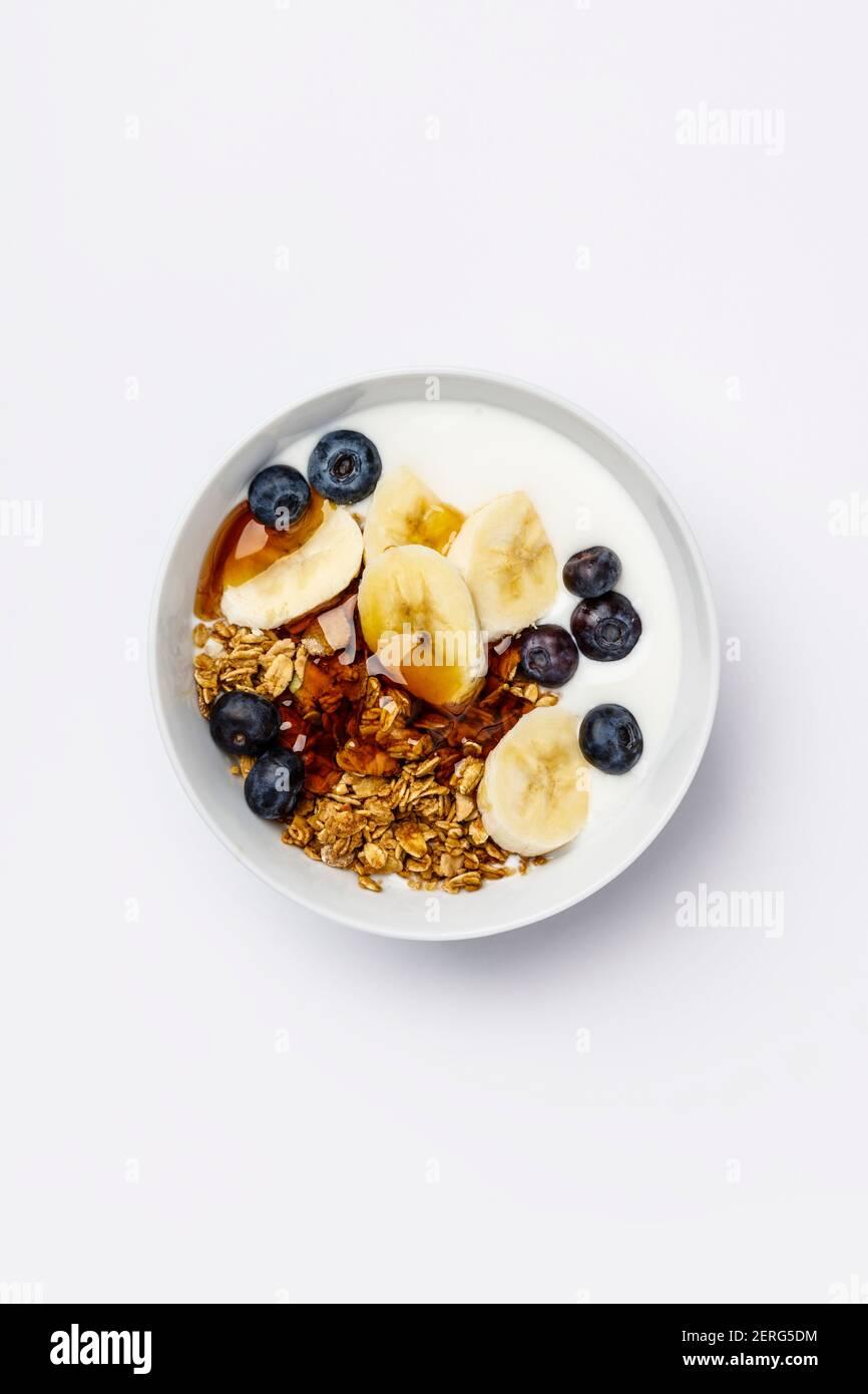 Le petit-déjeuner végétarien sain- avec des bleuets frais granola Avoine, banane, Yaourt de soja et le sirop d'érable sur fond blanc, télévision, vue d'en haut Banque D'Images