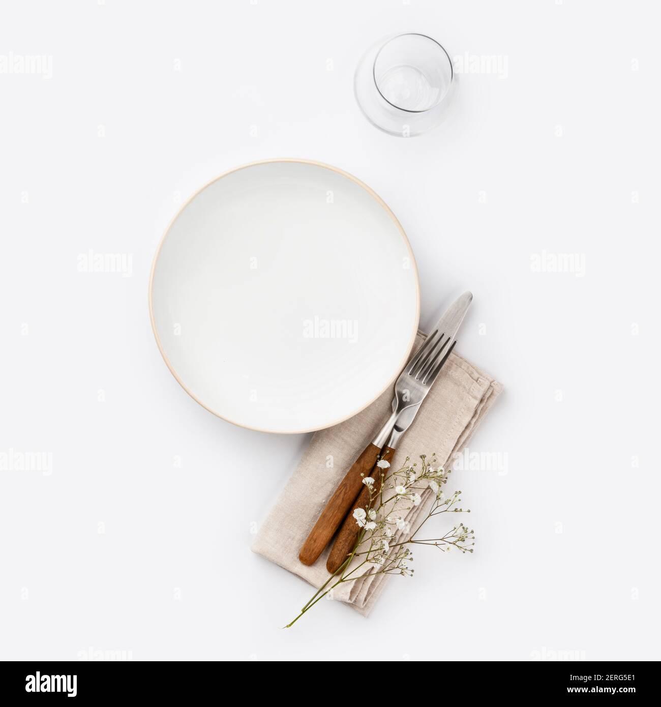 Plaque blanche vide et couverts sur une serviette, télévision mise sur fond blanc Banque D'Images