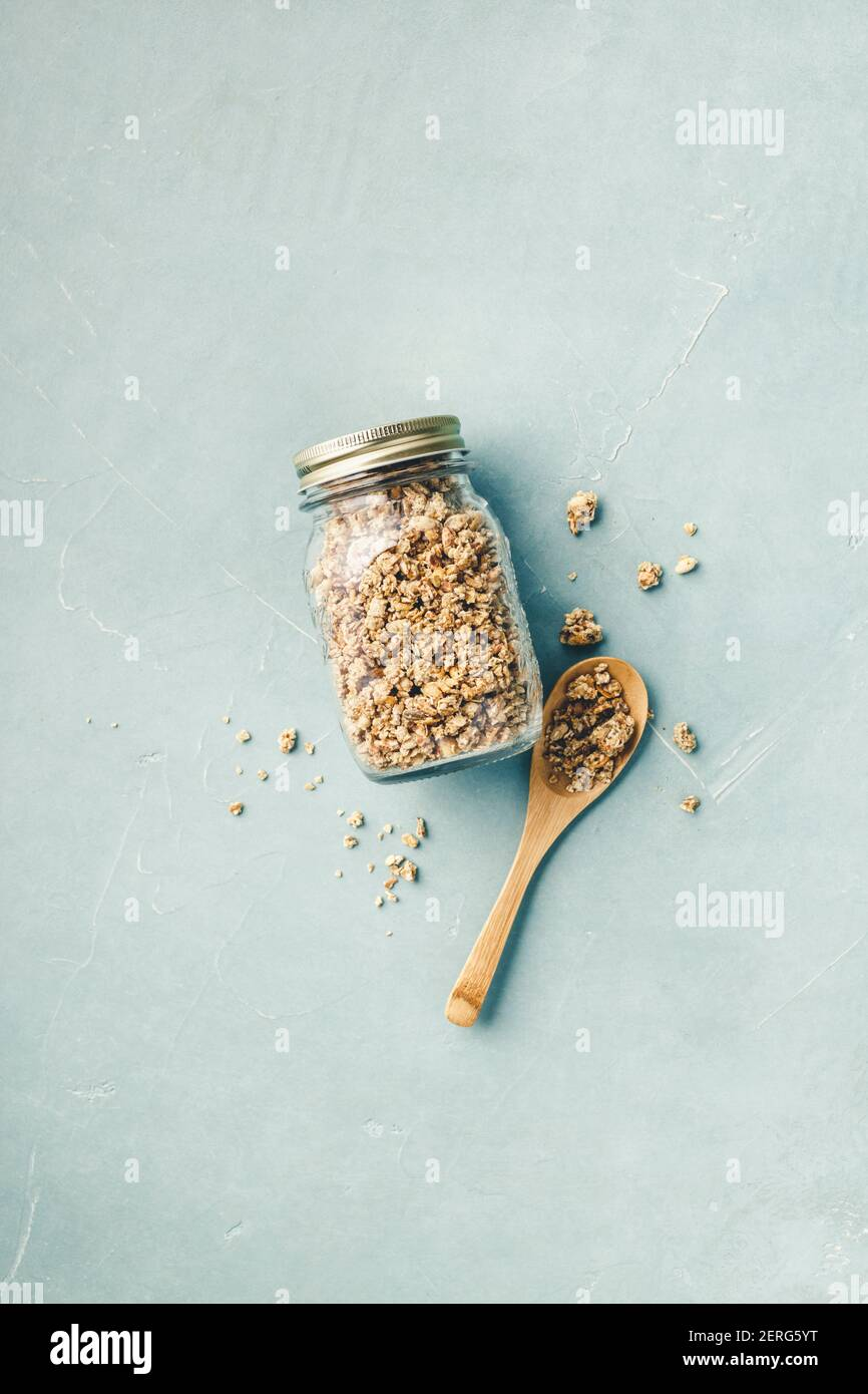 Granola maison dans un bocal en verre bleu sur fond de béton.Healthy snack vegan. Mise à plat Banque D'Images