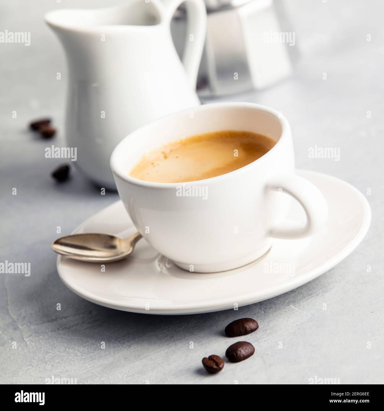 La composition du café sur fond blanc en béton. Dans l'Espresso Café tasse blanche avec du lait et une cafetière. Concept de petit-déjeuner Banque D'Images