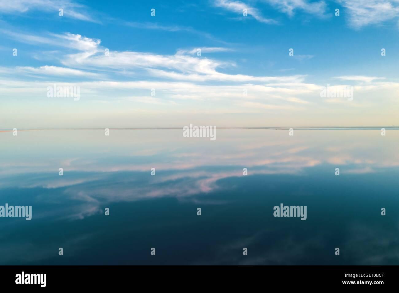 Eau de lac salée sous ciel bleu avec des nuages moelleux en été. Concept de couleur créative Banque D'Images