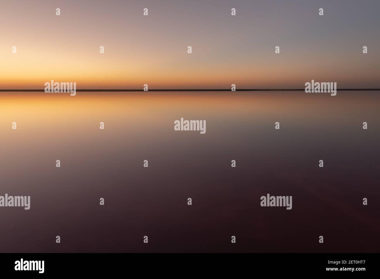 Paysage minimaliste tranquille avec surface lisse du lac salé rose avec eau calme avec horizon avec ciel clair au coucher du soleil. Simple beau naturel calme fond Banque D'Images