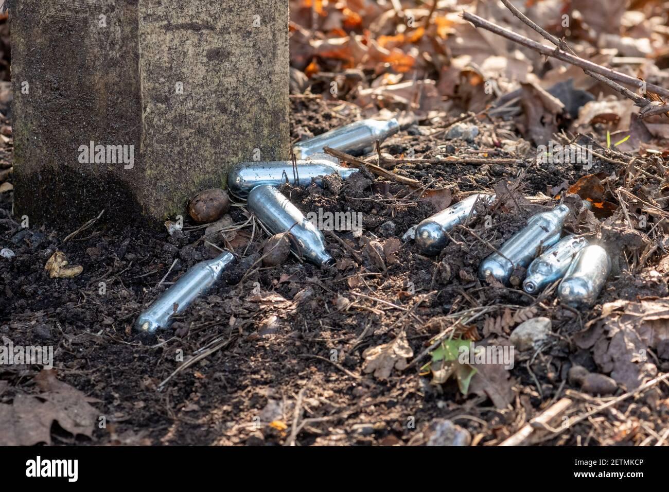 Bidons d'oxyde nitreux brillants (gaz riant) rejeté dans la campagne par des jeunes irresponsables Banque D'Images