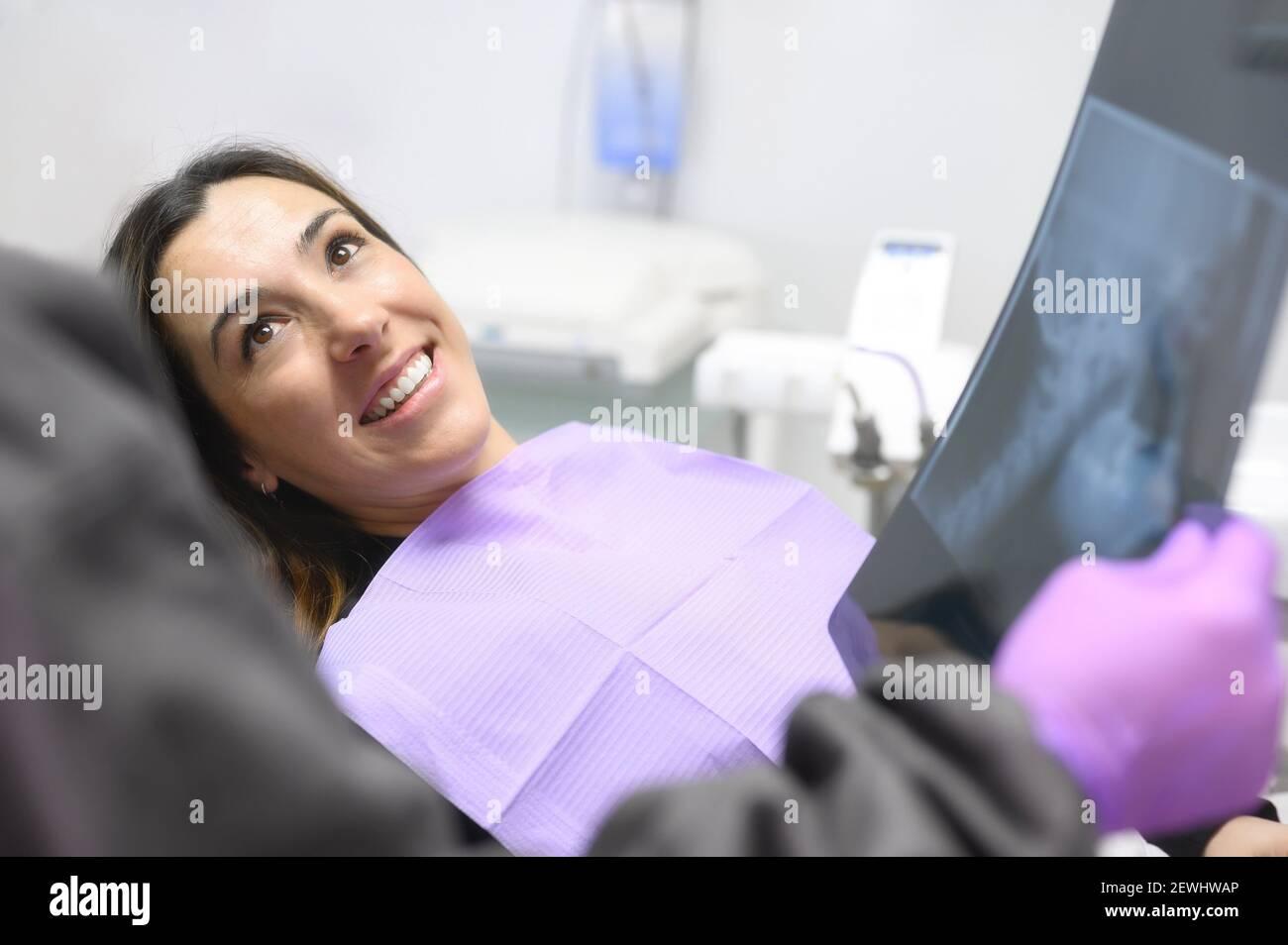 Bonne jeune femme, lors de la consultation avec le dentiste montrant des rayons X dans le cabinet dentaire. Photo de haute qualité. Banque D'Images