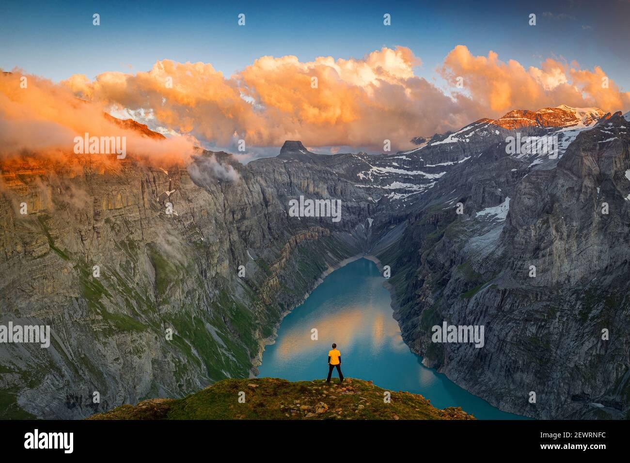 Homme debout sur des rochers regardant les nuages au coucher du soleil sur le lac Limmernsee, vue aérienne, canton de Glaris, Suisse, Europe Banque D'Images