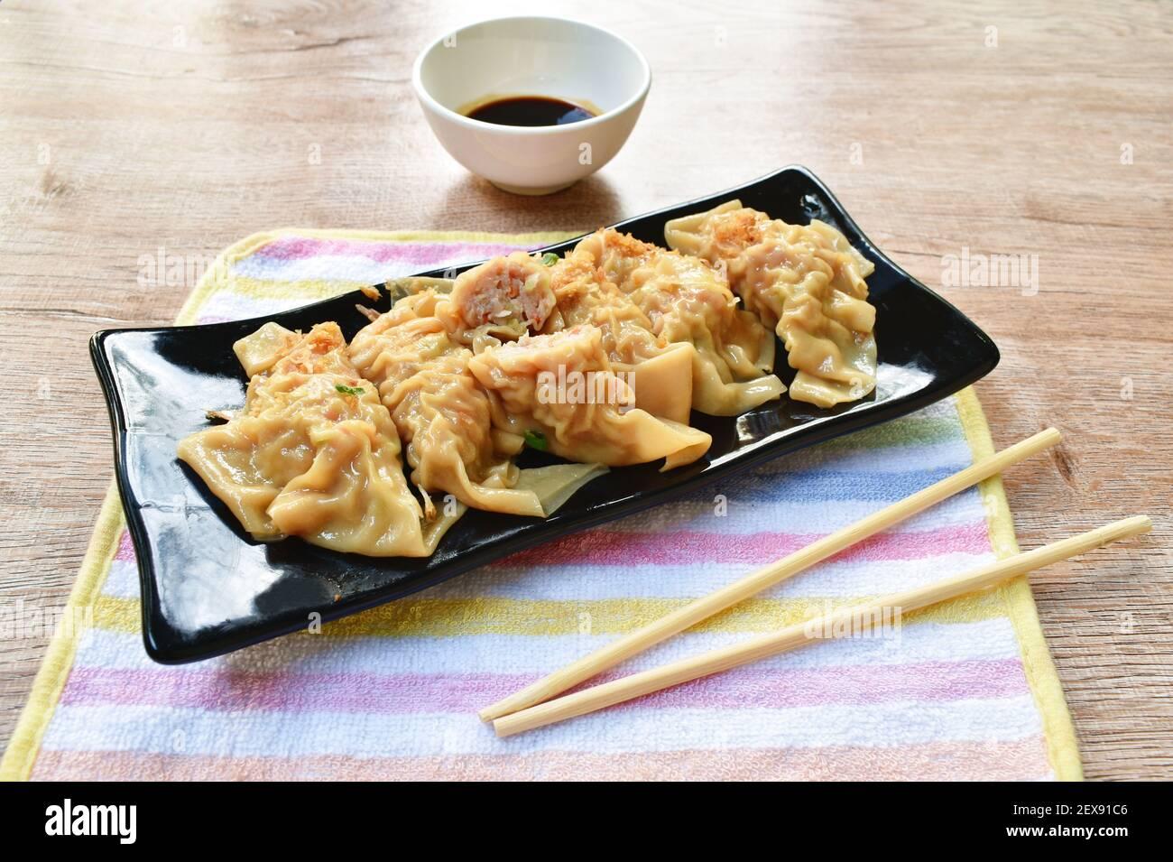 boulettes bouillies ou gyoza farcies écrasées de porc et de crevettes avec garniture de légumes frit, hacher l'ail sur une assiette en trempant le soja doux sauce Banque D'Images