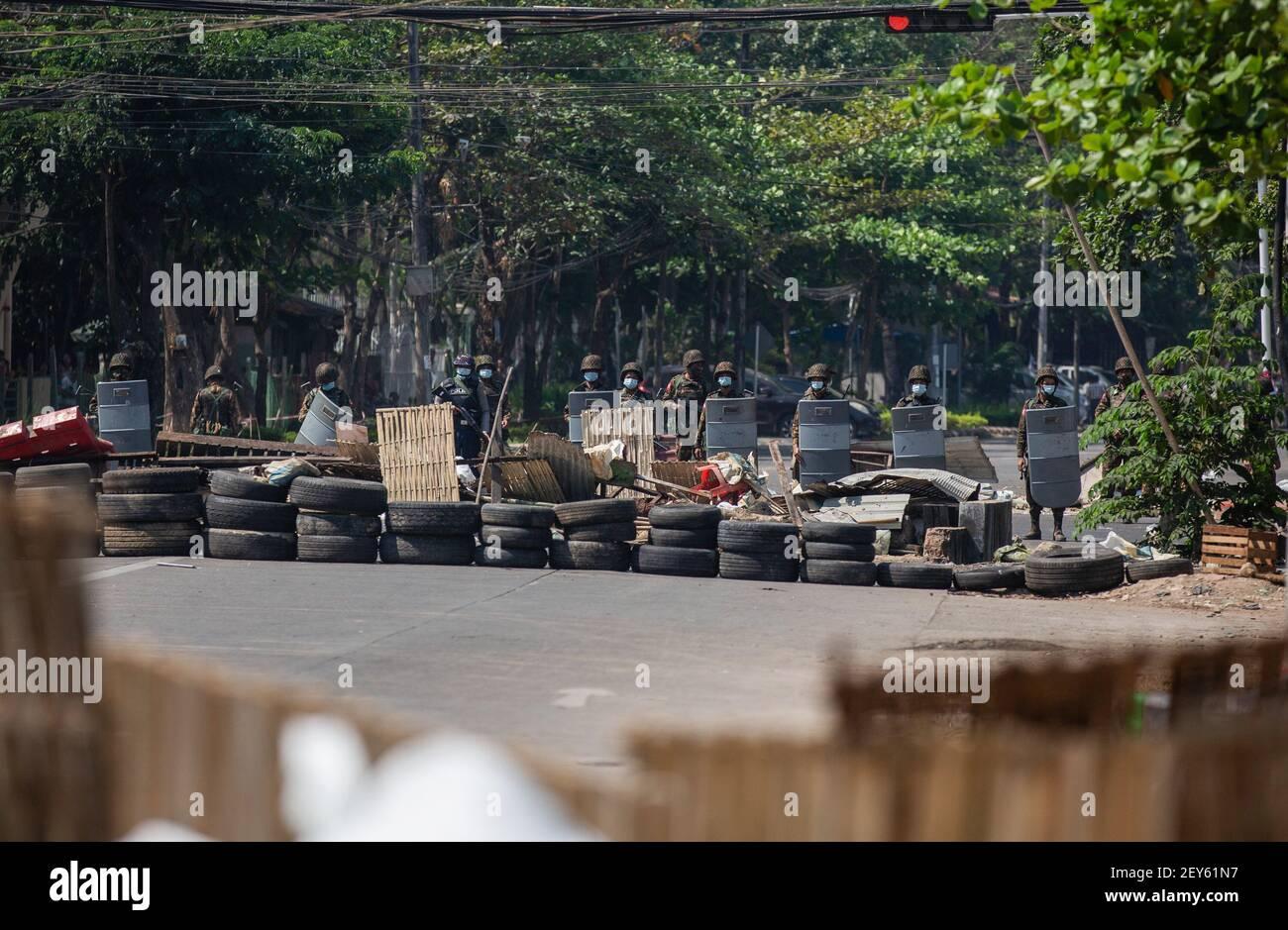 Des soldats et des policiers surveillent les barricades de fortune érigées par les manifestants pendant la manifestation. La police du Myanmar a tiré des balles en caoutchouc, des gaz lacrymogènes et des bombes sonores contre des manifestants pacifiques anti-coup militaire. Plusieurs ont été arrêtés et blessés, y compris des volontaires de secours, mais le nombre exact reste incertain. L'armée du Myanmar a arrêté le conseiller d'État du Myanmar Aung San Suu Kyi le 01 février 2021 et a déclaré l'état d'urgence tout en prenant le pouvoir dans le pays pendant un an après avoir perdu les élections contre la Ligue nationale pour la démocratie (NLD). Banque D'Images