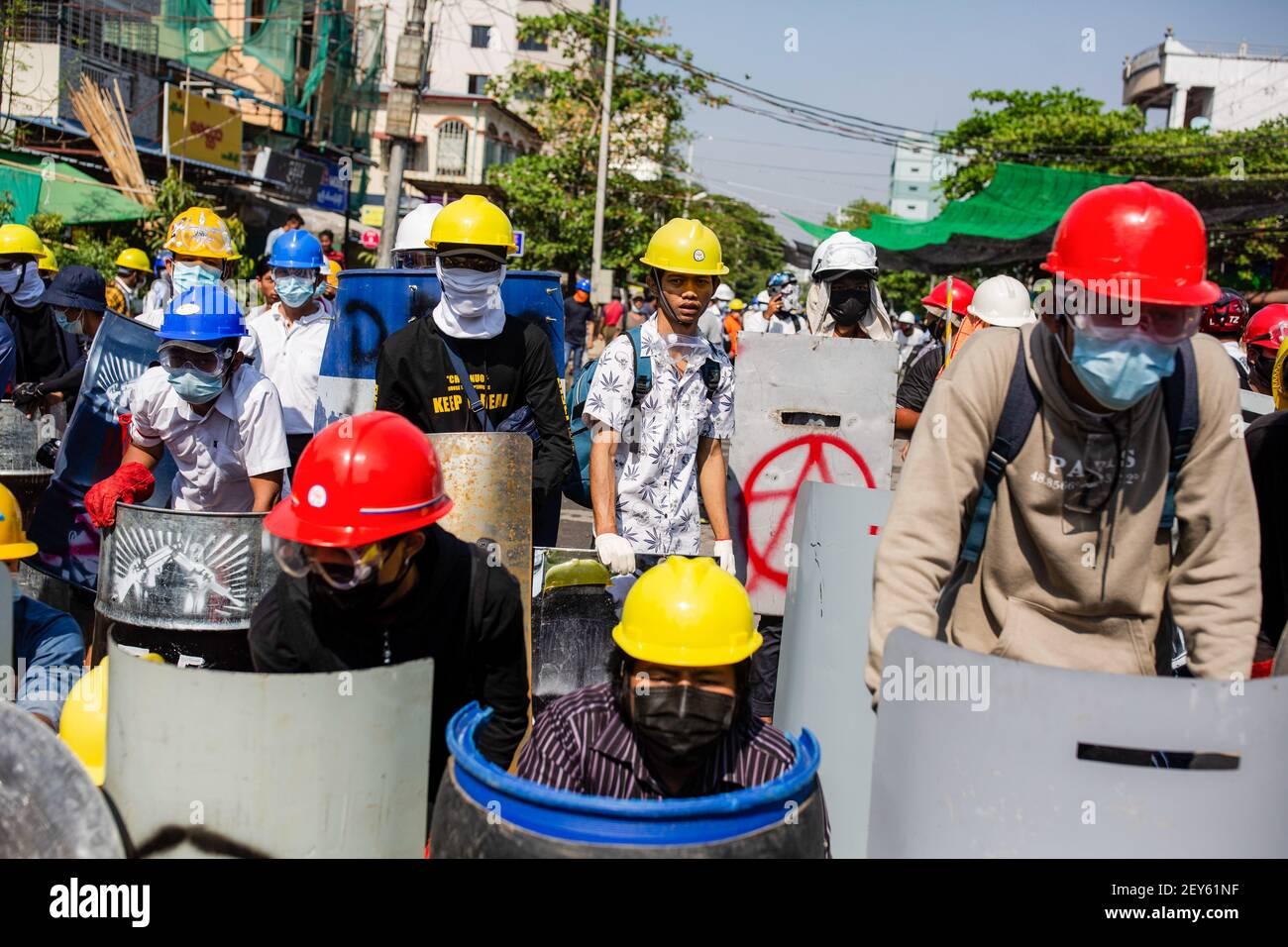 Les manifestants se cachent derrière des boucliers de fortune alors qu'ils se préparent à affronter les forces de sécurité pendant la manifestation. La police du Myanmar a tiré des balles en caoutchouc, des gaz lacrymogènes et des bombes sonores contre des manifestants pacifiques anti-coup militaire. Plusieurs ont été arrêtés et blessés, y compris des volontaires de secours, mais le nombre exact reste incertain. L'armée du Myanmar a arrêté le conseiller d'État du Myanmar Aung San Suu Kyi le 01 février 2021 et a déclaré l'état d'urgence tout en prenant le pouvoir dans le pays pendant un an après avoir perdu les élections contre la Ligue nationale pour la démocratie (NLD). Banque D'Images