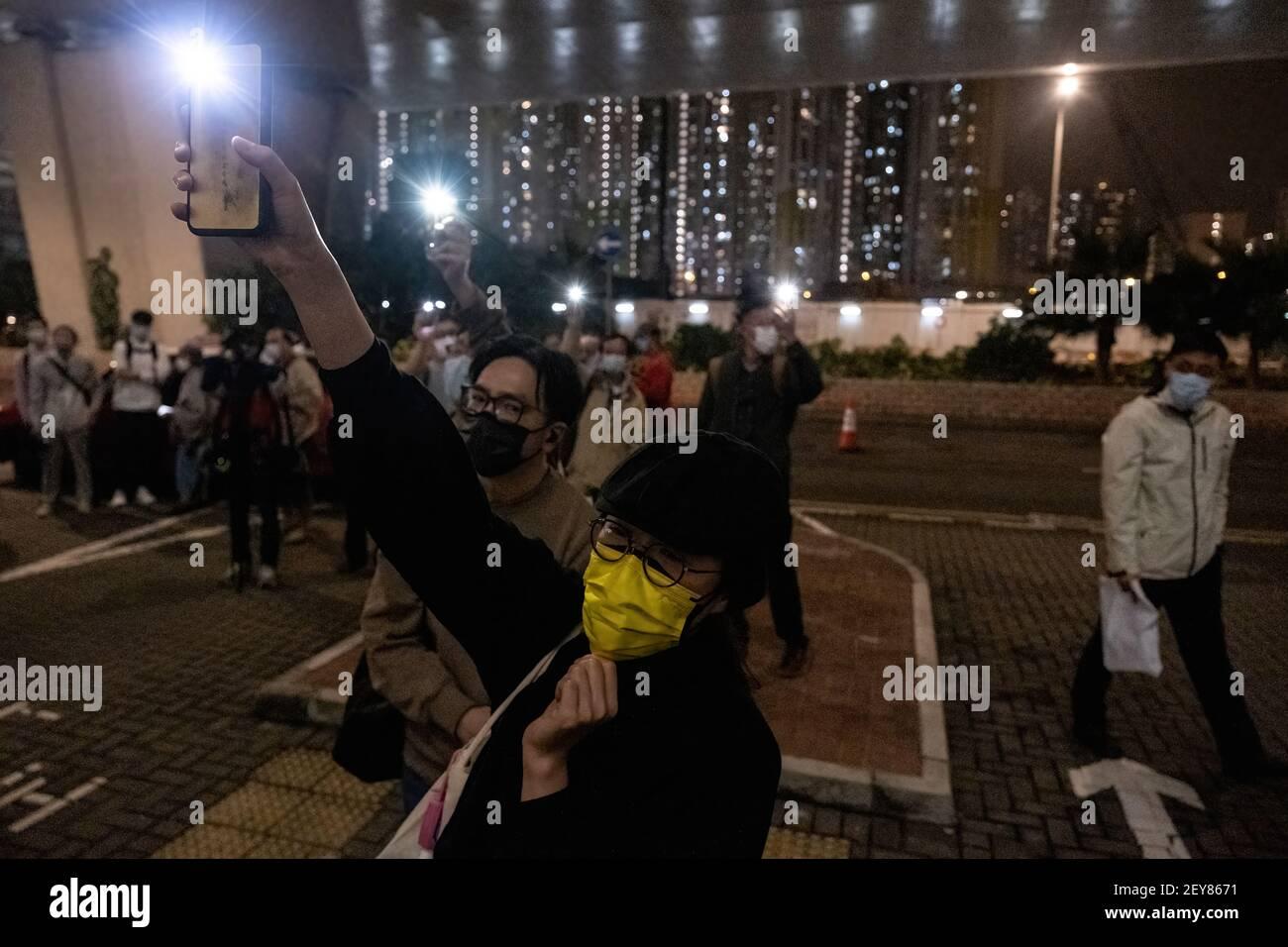 Un défenseur de la militante pro-démocratie agite sa lumière de téléphone cellulaire devant la cour de Kowloon Ouest.quatre des 47 militants pro-démocratie accusés de subversion en vertu de la loi de sécurité nationale sont libérés sous caution, Après que le ministère de la Justice a retiré son appel de la décision du tribunal de leur accorder la caution et de 11 autres personnes. Banque D'Images