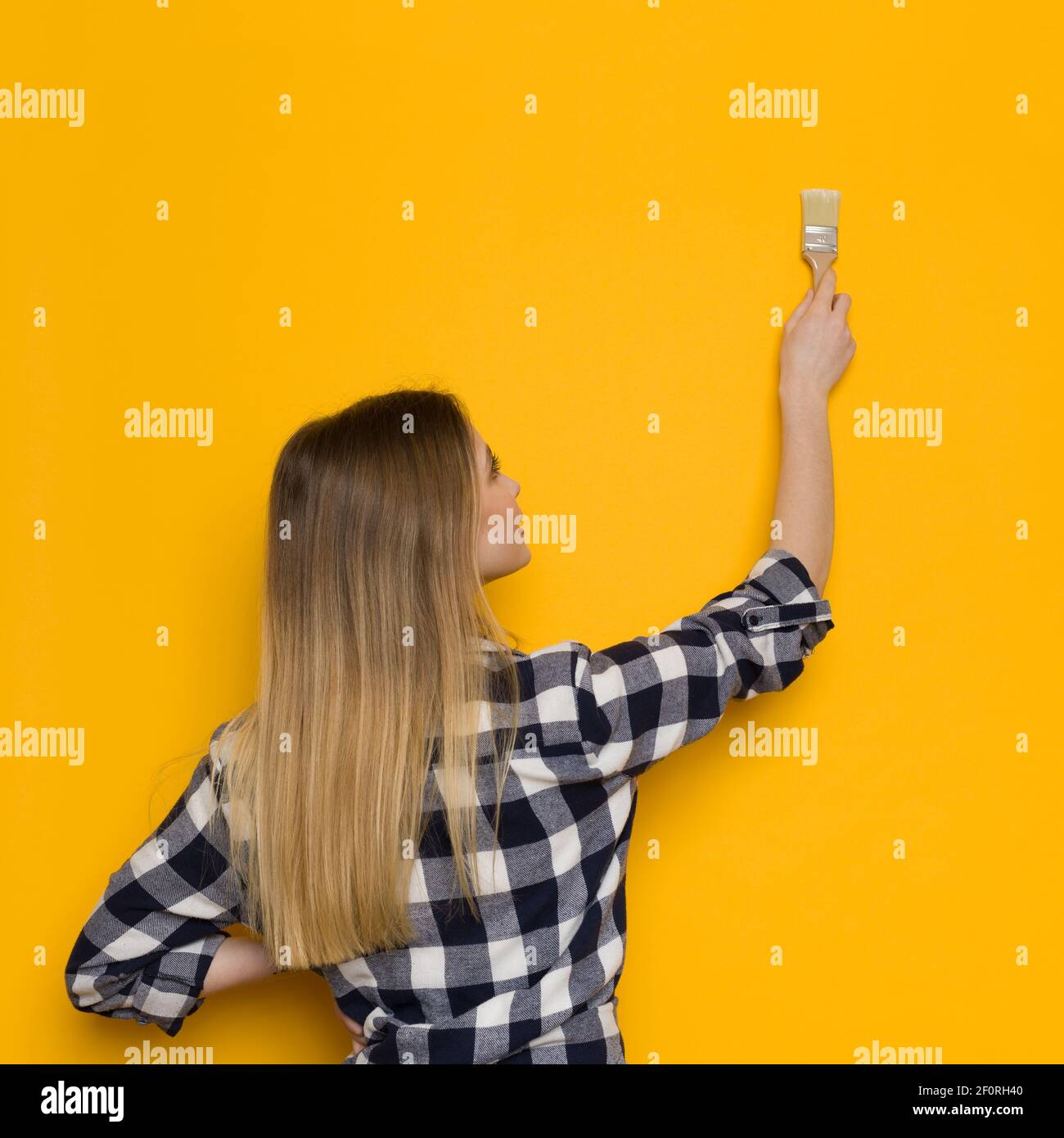La jeune femme blonde en chemise de bûcherons peint un mur jaune. Vue arrière. Taille haute. Banque D'Images