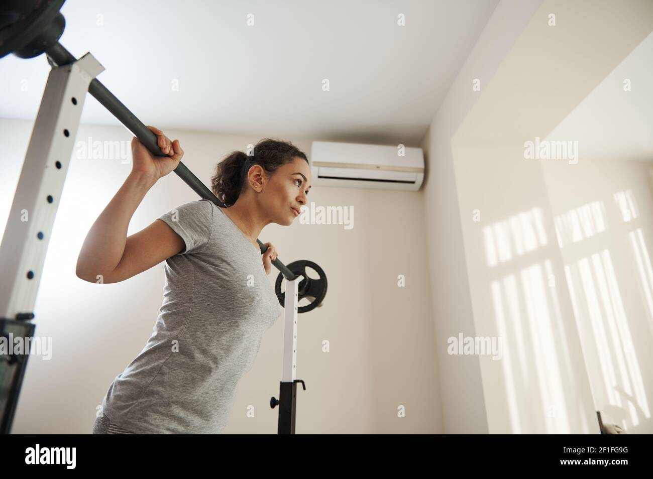 Belle femme s'entraîner avec un barbell à la maison. Concept de mode de vie actif et sain Banque D'Images