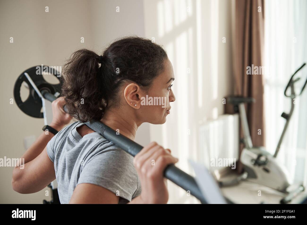 Vue arrière de la jeune femme sportive afro-américaine qui fait de l'exercice avec un squat lourd et une barbell dans la salle de gym à la maison. Entraînement lourd. Banque D'Images