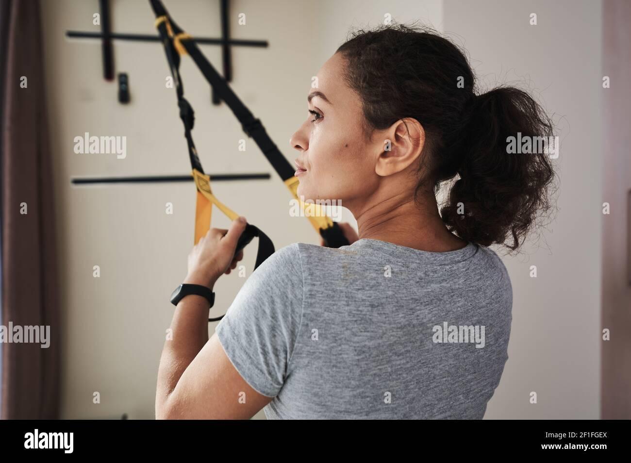 Gros plan sur le côté d'une jeune femme effectuant un entraînement fonctionnel avec des sangles de fitness. Style de vie sain, entraînement à l'intérieur, entraînement fonctionnel. Banque D'Images