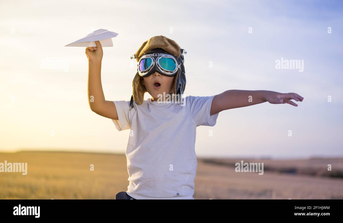 Little Boy wearing helmet et rêve de devenir un aviateur pendant la lecture d'un avion en papier au coucher du soleil Banque D'Images