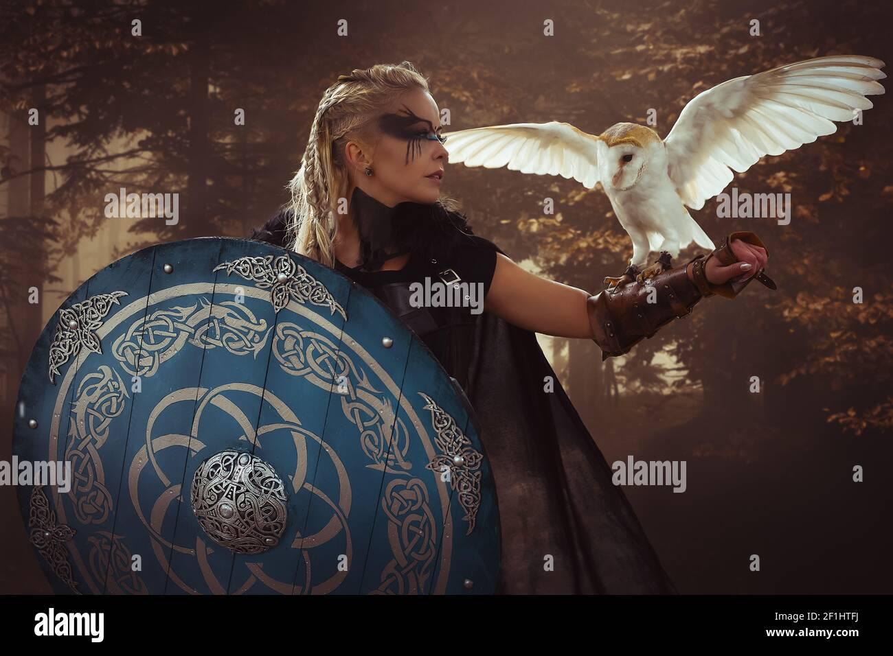 Guerrier, belle chouette blanche, Viking blond woman avec le bouclier et l'épée, de tresses dans ses cheveux. Banque D'Images
