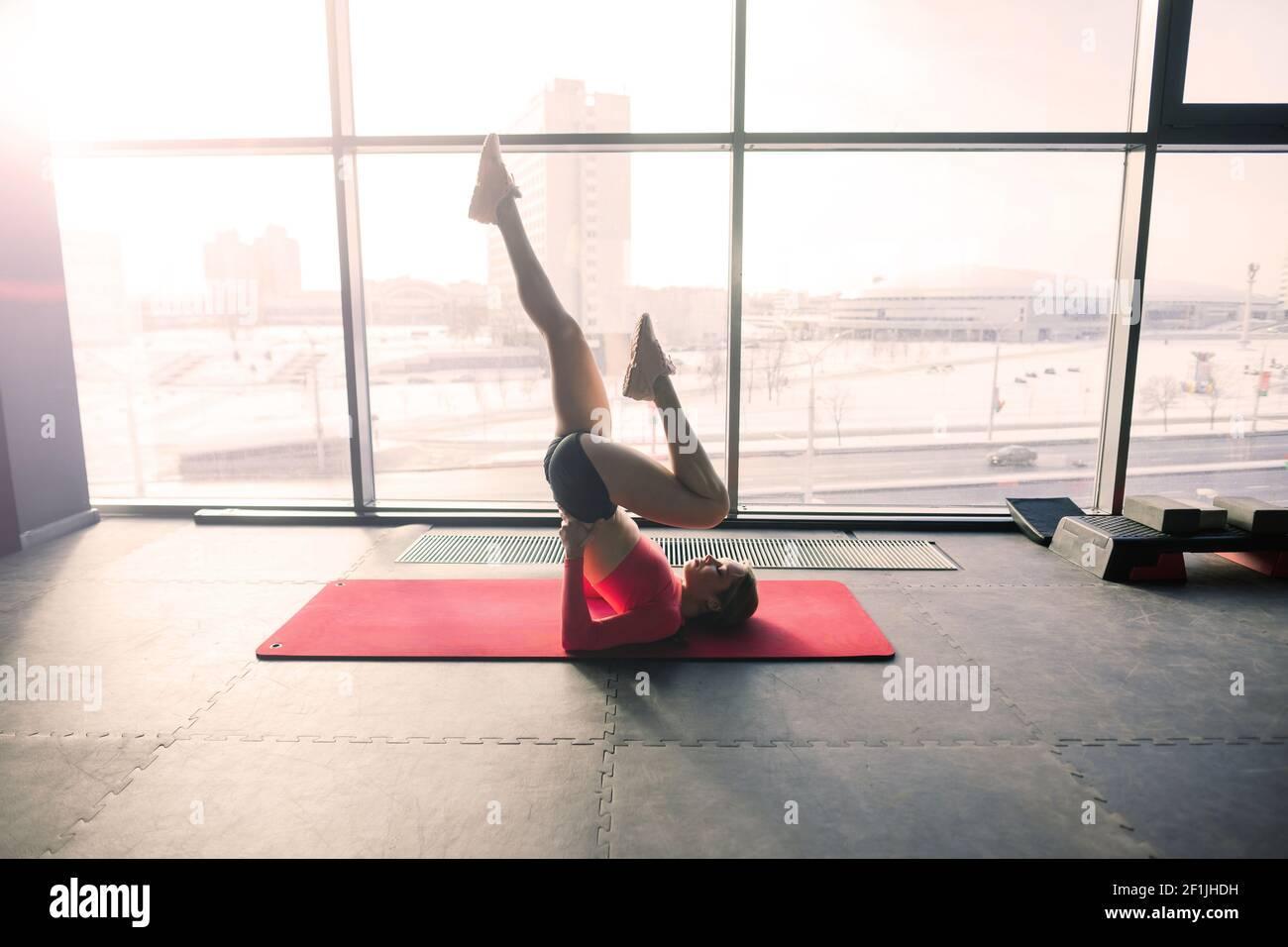 Femme pratiquant le yoga avancé sur un tapis contre une grande fenêtre Banque D'Images