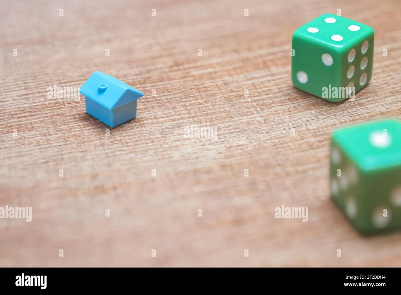 Notion de risques et de chances de propriété. Maison miniature et dés sur fond de bois prêts hypothécaires impôts immobiliers et dettes. Symbol investissement dans la maison Banque D'Images