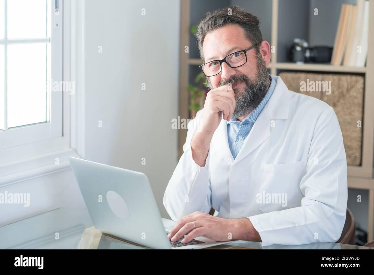 Un vieux médecin souriant en lunettes et un uniforme blanc s'assoir à l'hôpital sur un ordinateur portable écrire dans le journal, un homme mature heureux médecin de premier plan remplir p Banque D'Images