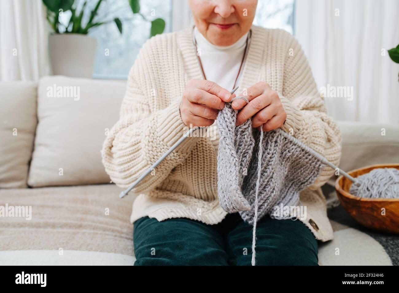 Joyeux granny assis sur un canapé à la maison, tricotage avec des aiguilles, avec de la laine grise. Pantacourt, demi-visage. Banque D'Images