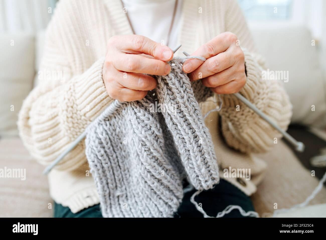 Granny assis sur un canapé à la maison, tricotage avec des aiguilles, avec de la laine grise. Rogné, pas de visage. Banque D'Images