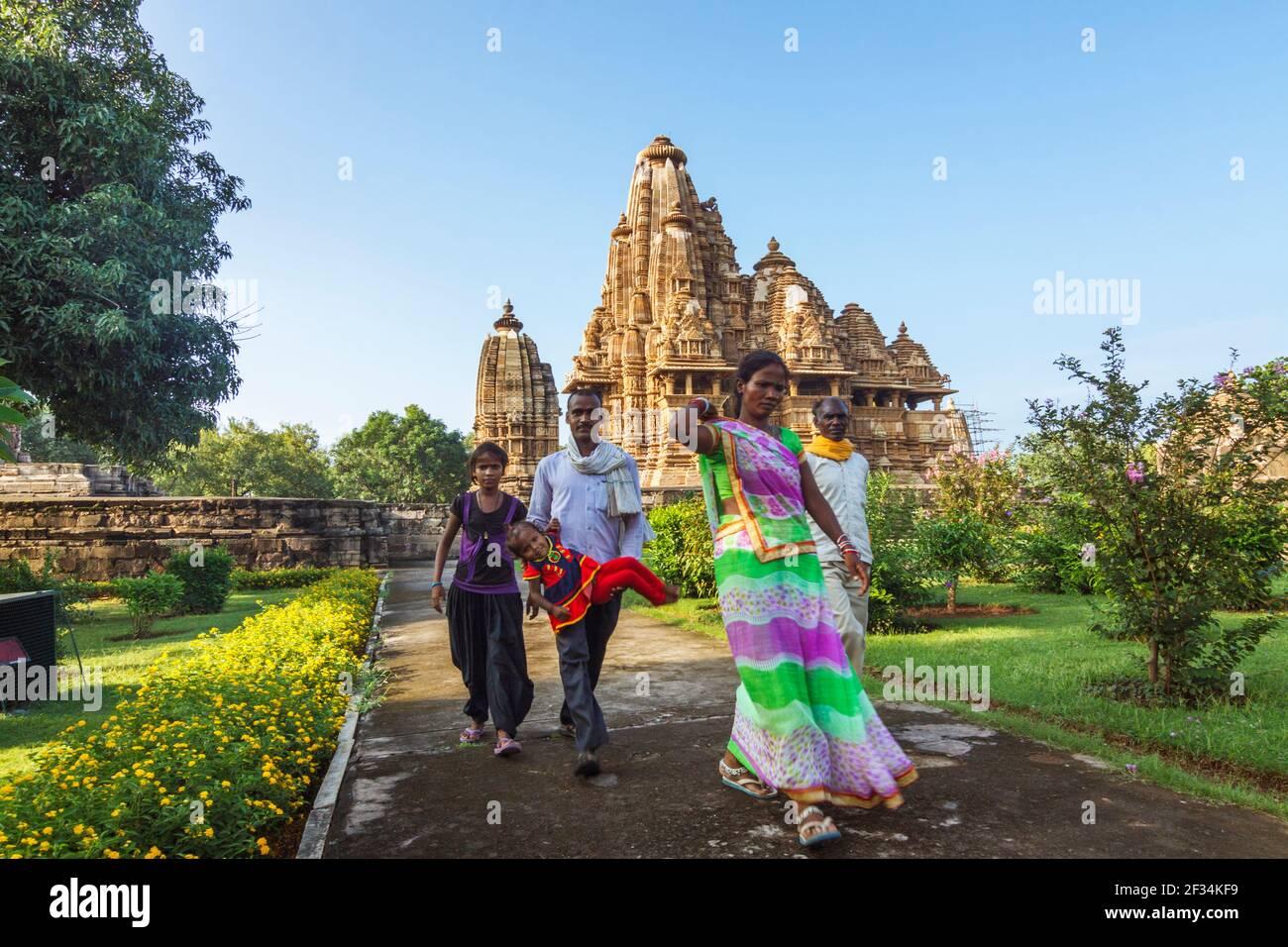 Khajuraho, Madhya Pradesh, Inde : une famille indienne passe devant le temple Lakshmana du Xe siècle, partie du groupe occidental de l'UNESCO World Heritag Banque D'Images