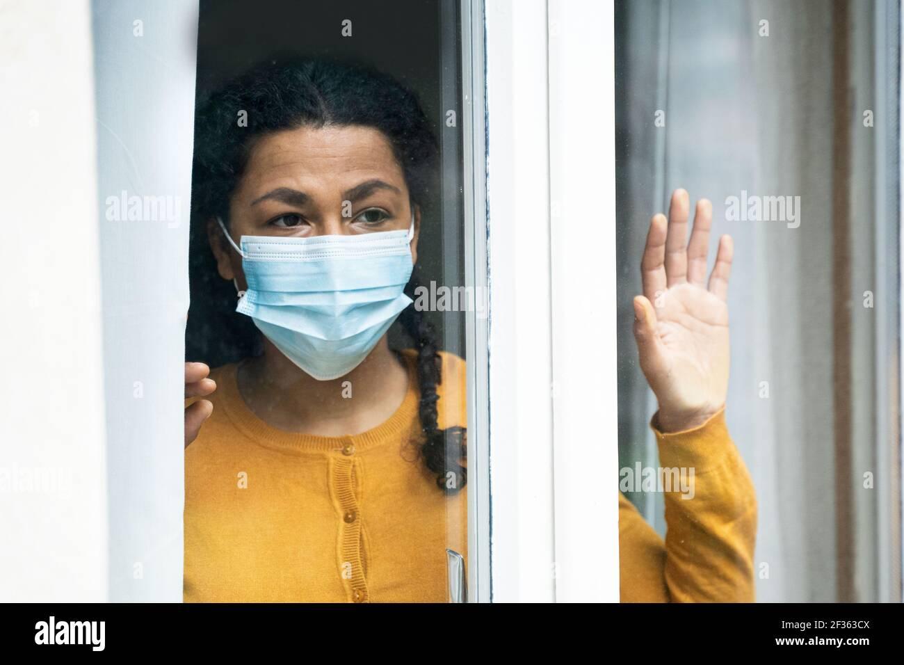 Femme noire inquiète en regardant par la fenêtre Banque D'Images