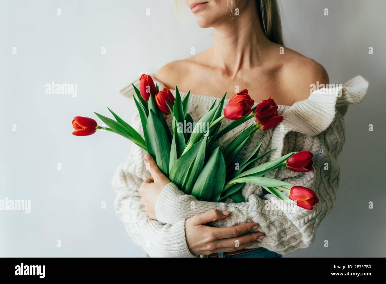 Une jeune femme tient un magnifique bouquet de tulipes rouges dans ses mains. Banque D'Images
