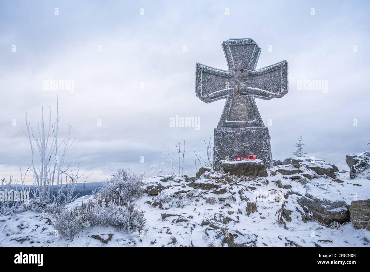 Croix de guerre en pierre près de la tour de belvédère Stepanka, à la frontière des monts Krkonose et Jizera. Jour couvert d'hiver, ciel avec nuages, arbres couverts Banque D'Images