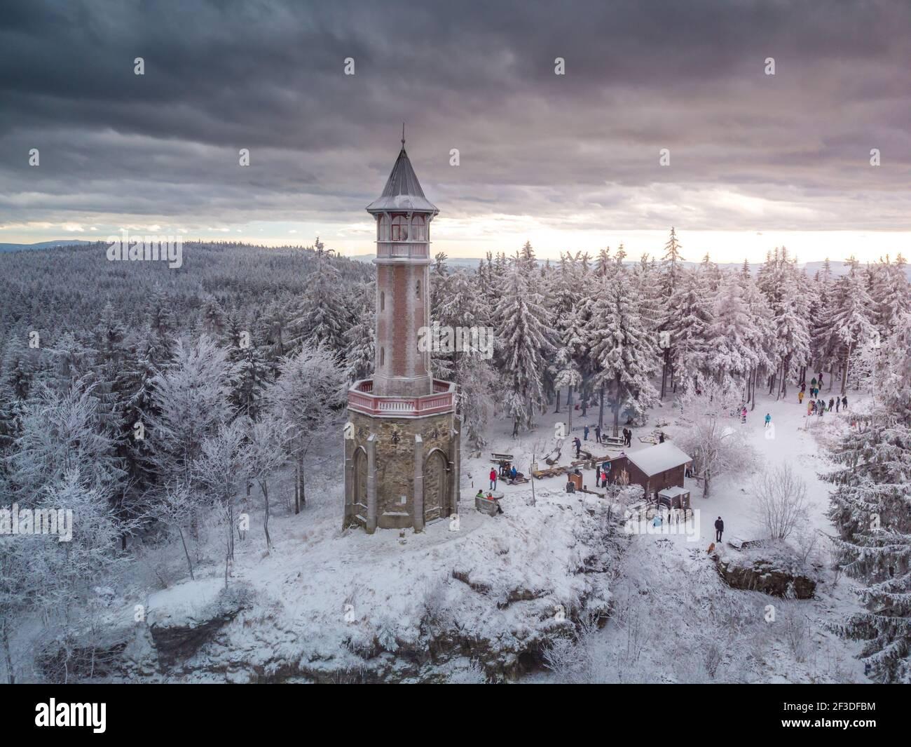 Photo aérienne de la tour Stepanka, à la frontière des montagnes Krkonose et Jizera. Jour couvert d'hiver, ciel avec nuages, arbres couverts de neige. Banque D'Images