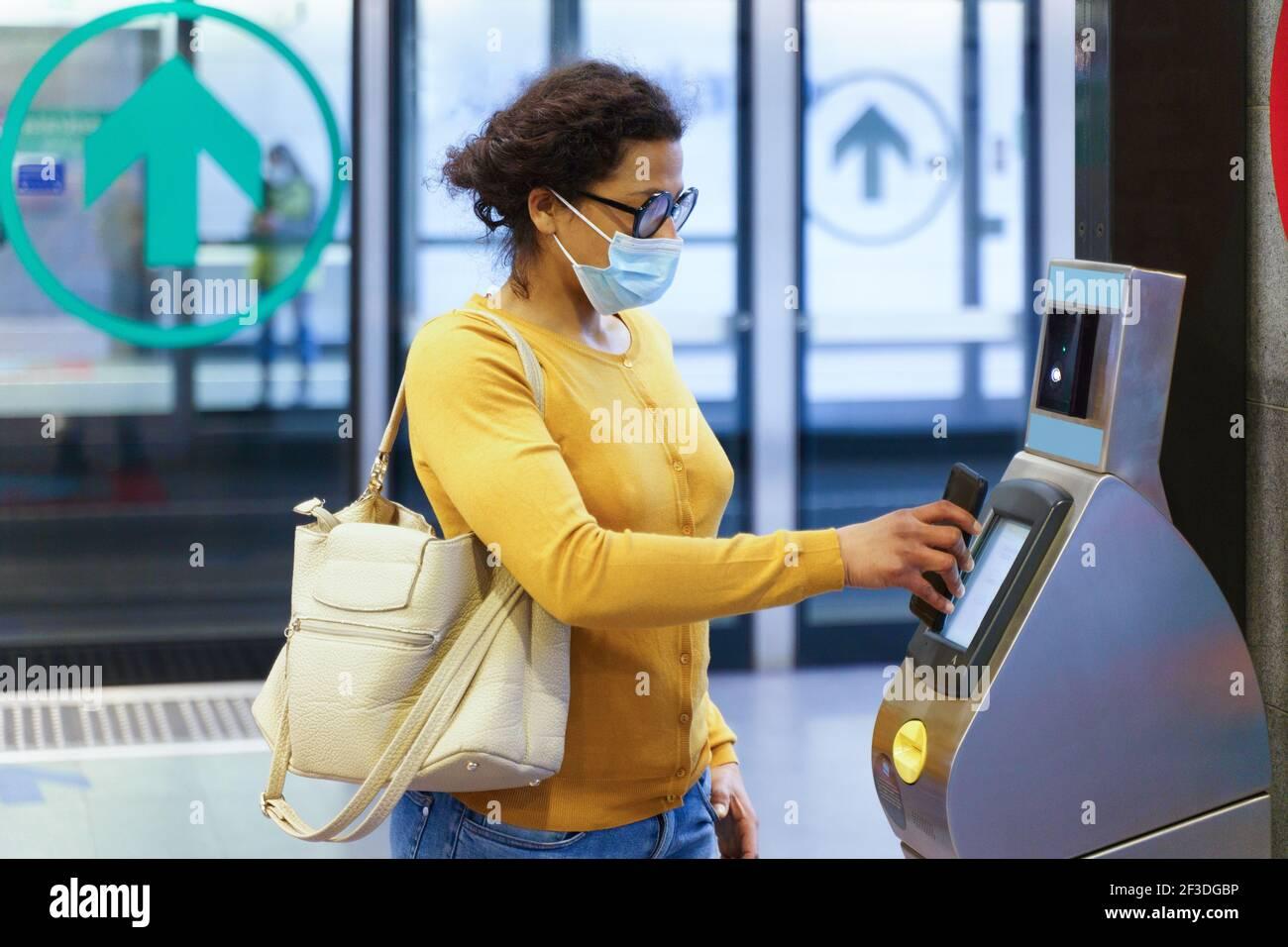 Femme payant le billet de transport à l'aide d'un smartphone et d'une machine sans contact Banque D'Images