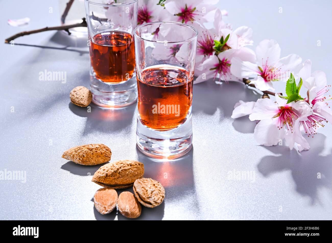 liqueur d'amande. La boisson traditionnelle forte en italie pour compléter le dîner est une liqueur à base de noix et de baies. Ratafia, alcool en grenaille. Vue de dessus sur la table et amandes en fleurs. Copier l'espace Banque D'Images