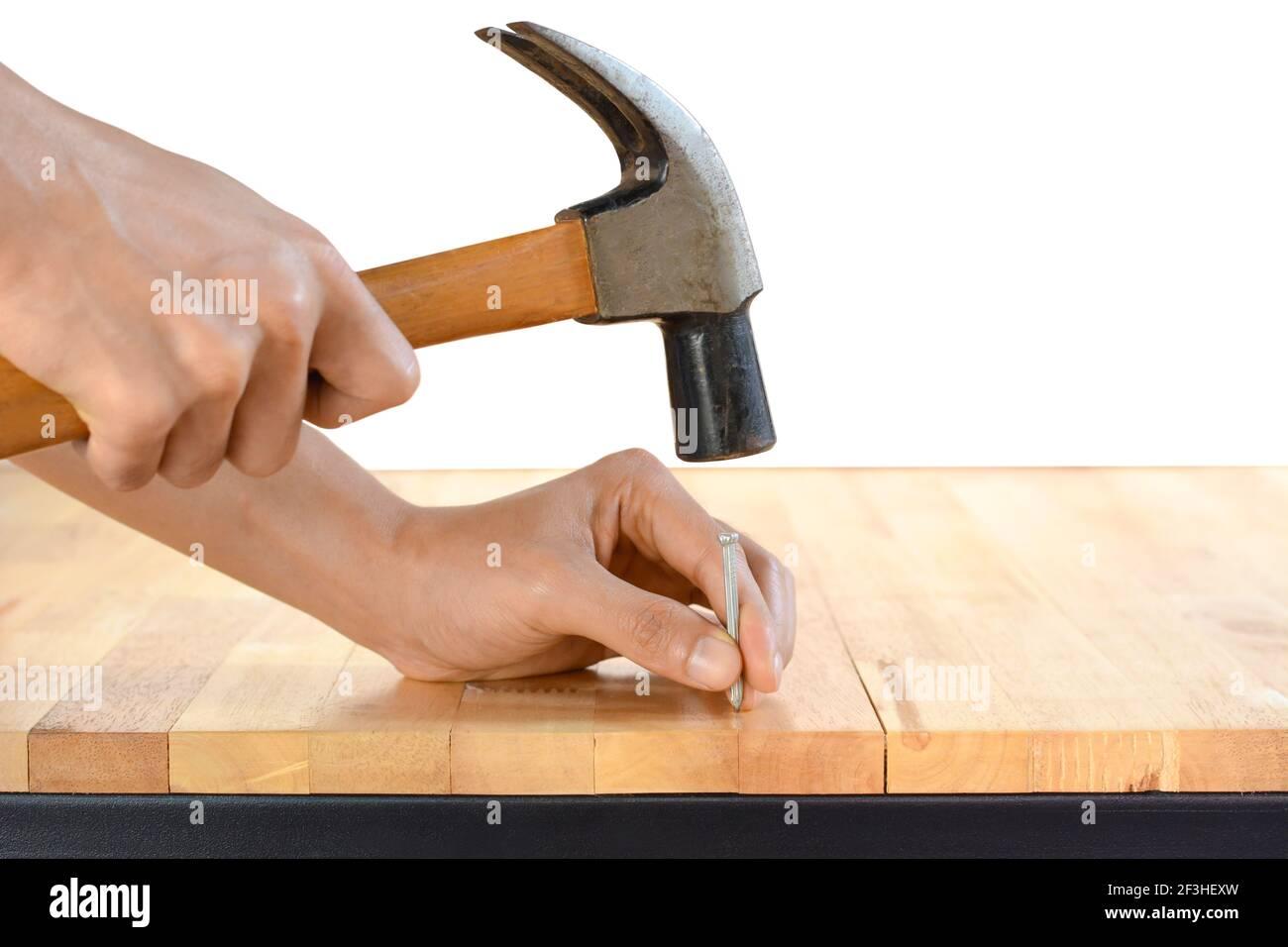 Marteler un clou à la main sur une table en bois Banque D'Images