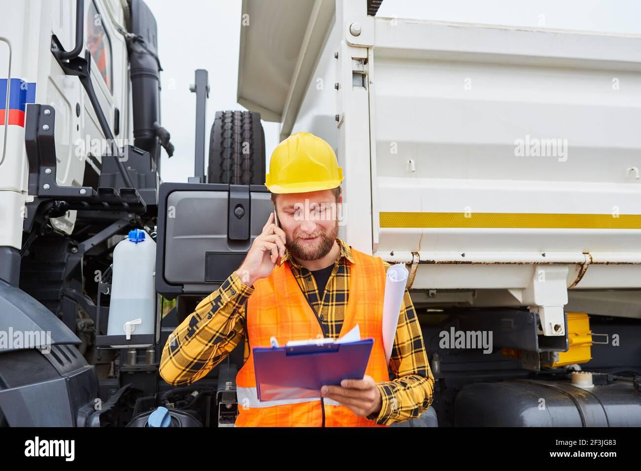 Travailleur de la construction ou chef de chantier avec liste de contrôle et smartphone dans avant du camion sur le chantier Banque D'Images