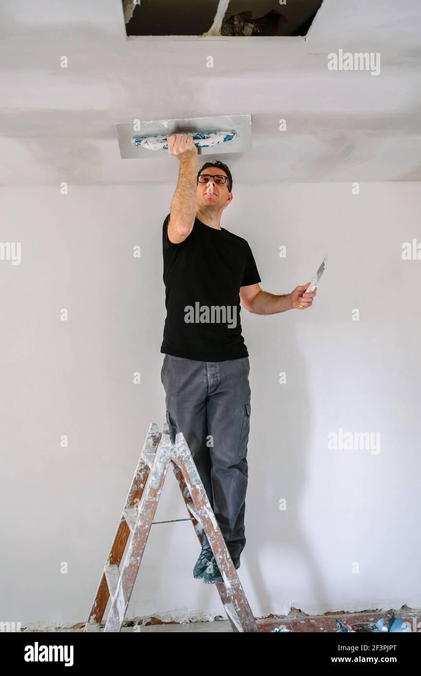 Plâtrier lissant le plafond en plâtre avec la truelle Banque D'Images