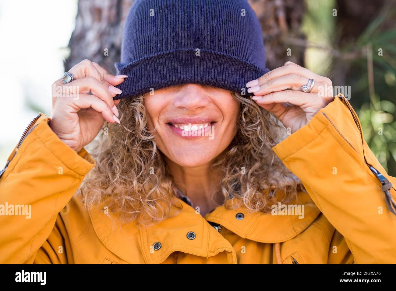Joyeux adulte beau portrait de femme couvrant ses yeux avec l'hiver tasse - les gens heureux profiter des activités de loisirs en plein air - joli sourire et dents concrènent Banque D'Images