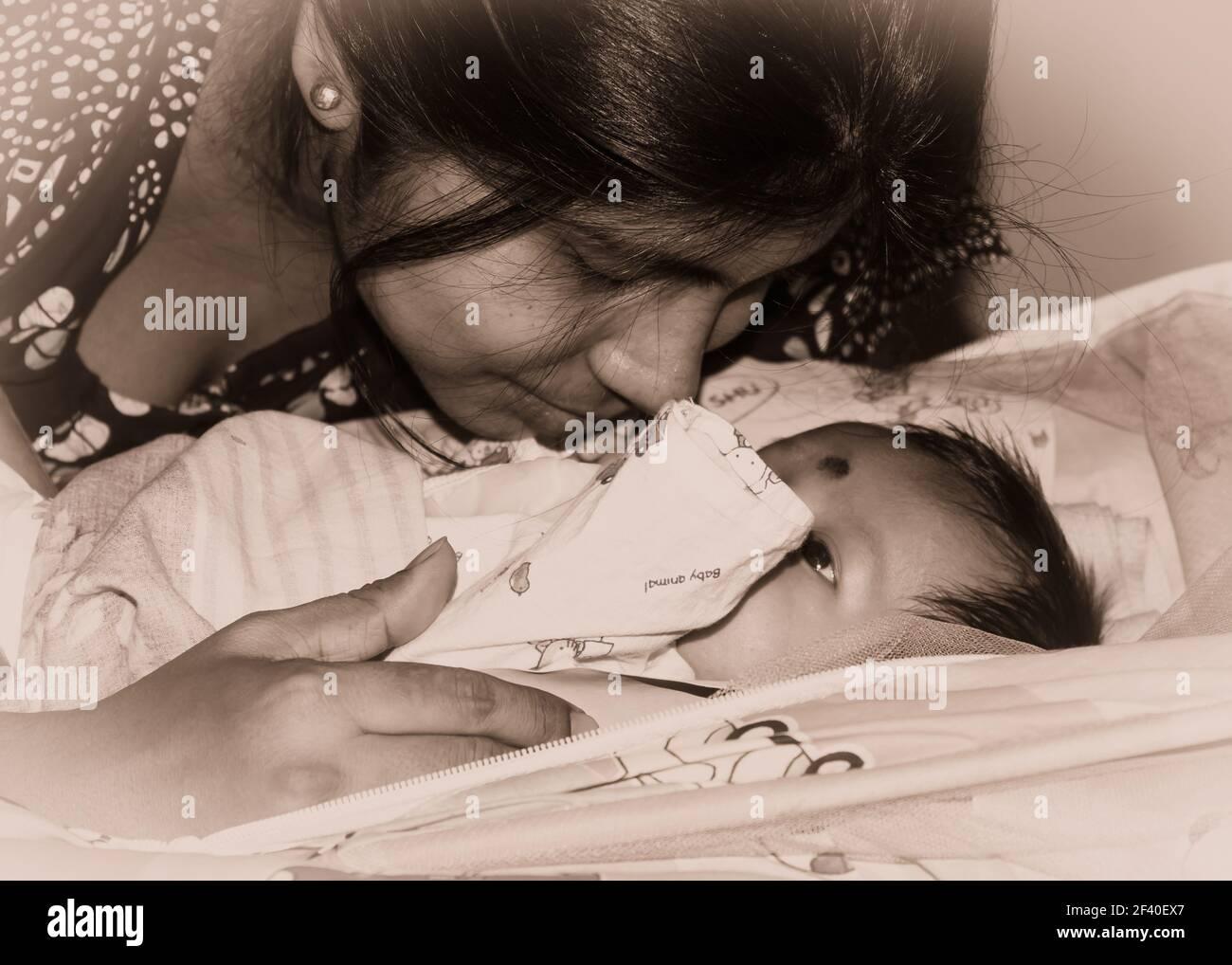 Adorable nouveau-né bébé garçon embrassé par la mère dans son tour de mère allongé sur le lit. Gros plan. Bébé Sweet Little d'un mois. Ethnie indienne. Vue avant Banque D'Images
