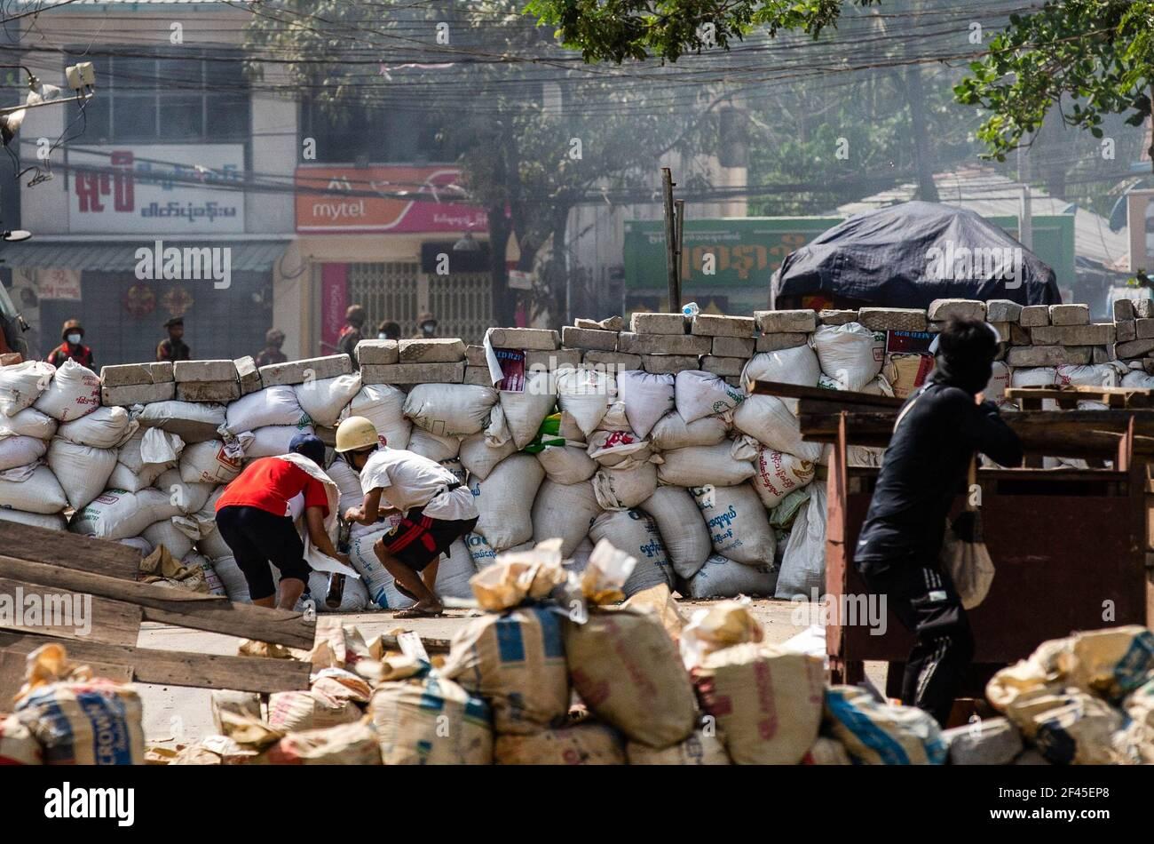 Les manifestants anti-coup d'Etat militaire se cachent derrière une barricade improvisée tout en tenant des cocktails molotov lors d'une manifestation contre le coup d'Etat militaire. La police et les militaires du Myanmar (tatmadow) ont attaqué les manifestants avec des balles en caoutchouc, des munitions réelles, des gaz lacrymogènes et des bombes lacrymogènes en réponse aux manifestants anti-coup d'État militaire de vendredi, tuant plusieurs manifestants et en blessant beaucoup d'autres. Au moins 149 personnes ont été tuées au Myanmar depuis le coup d'État du 1er février, a déclaré un responsable des droits de l'homme de l'ONU. L'armée du Myanmar a détenu le conseiller d'État du Myanmar Aung San Suu Kyi le 01 février 2021 et Banque D'Images