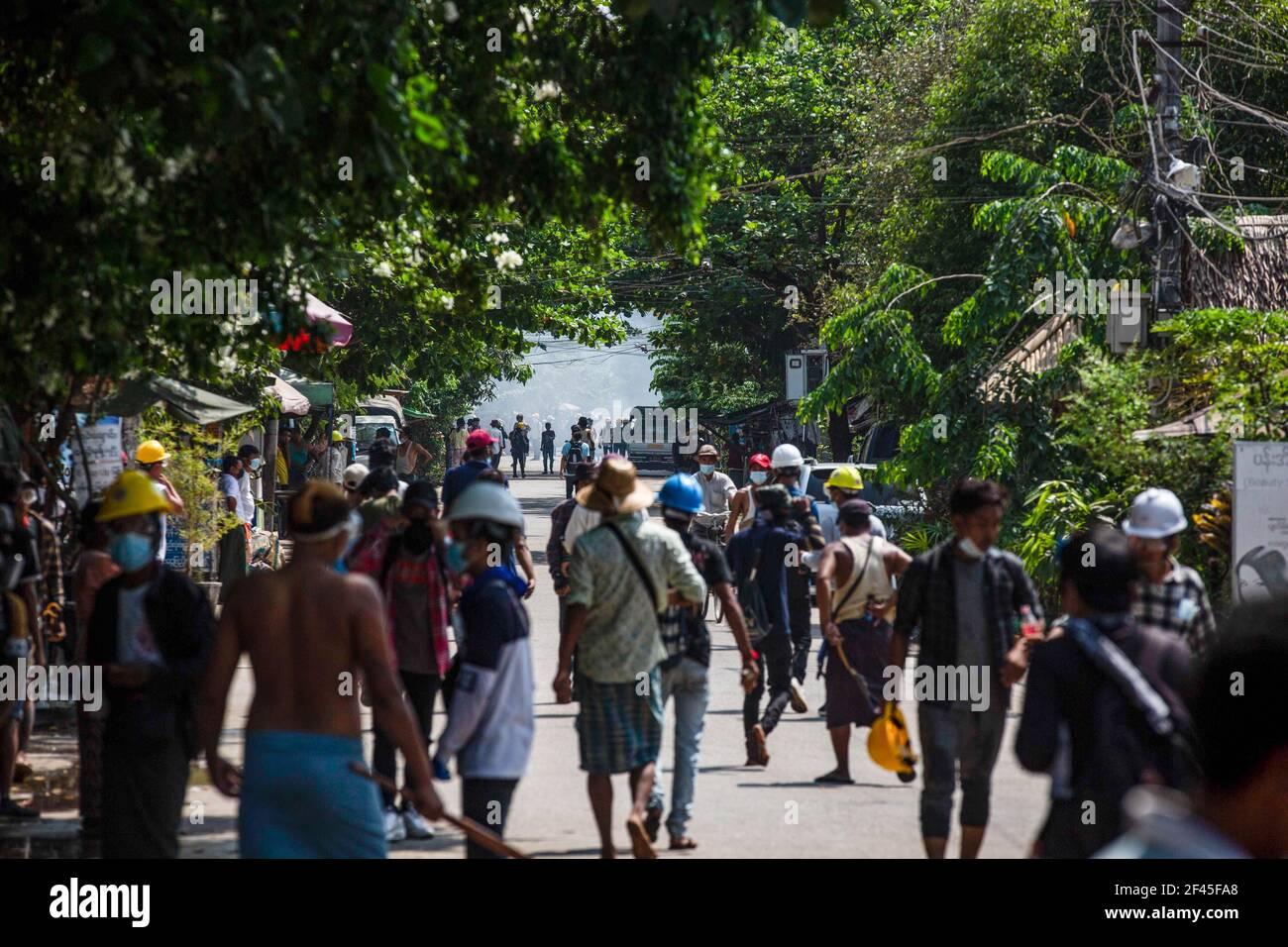 Les manifestants anti-coup d'Etat militaire se promeuvent vers les barricades improvisées au bout de la rue lors d'une manifestation contre le coup d'Etat militaire.la police et les militaires du Myanmar (tatmadow) ont attaqué les manifestants avec des balles en caoutchouc, des munitions réelles, des gaz lacrymogènes et des bombes lacrymogènes en réponse aux manifestants anti coup d'Etat militaire de vendredi, tuant plusieurs manifestants et en blessant beaucoup d'autres. Au moins 149 personnes ont été tuées au Myanmar depuis le coup d'État du 1er février, a déclaré un responsable des droits de l'homme de l'ONU. L'armée du Myanmar a détenu le conseiller d'État du Myanmar Aung San Suu Kyi le 01 février 2021 et a déclaré une Banque D'Images