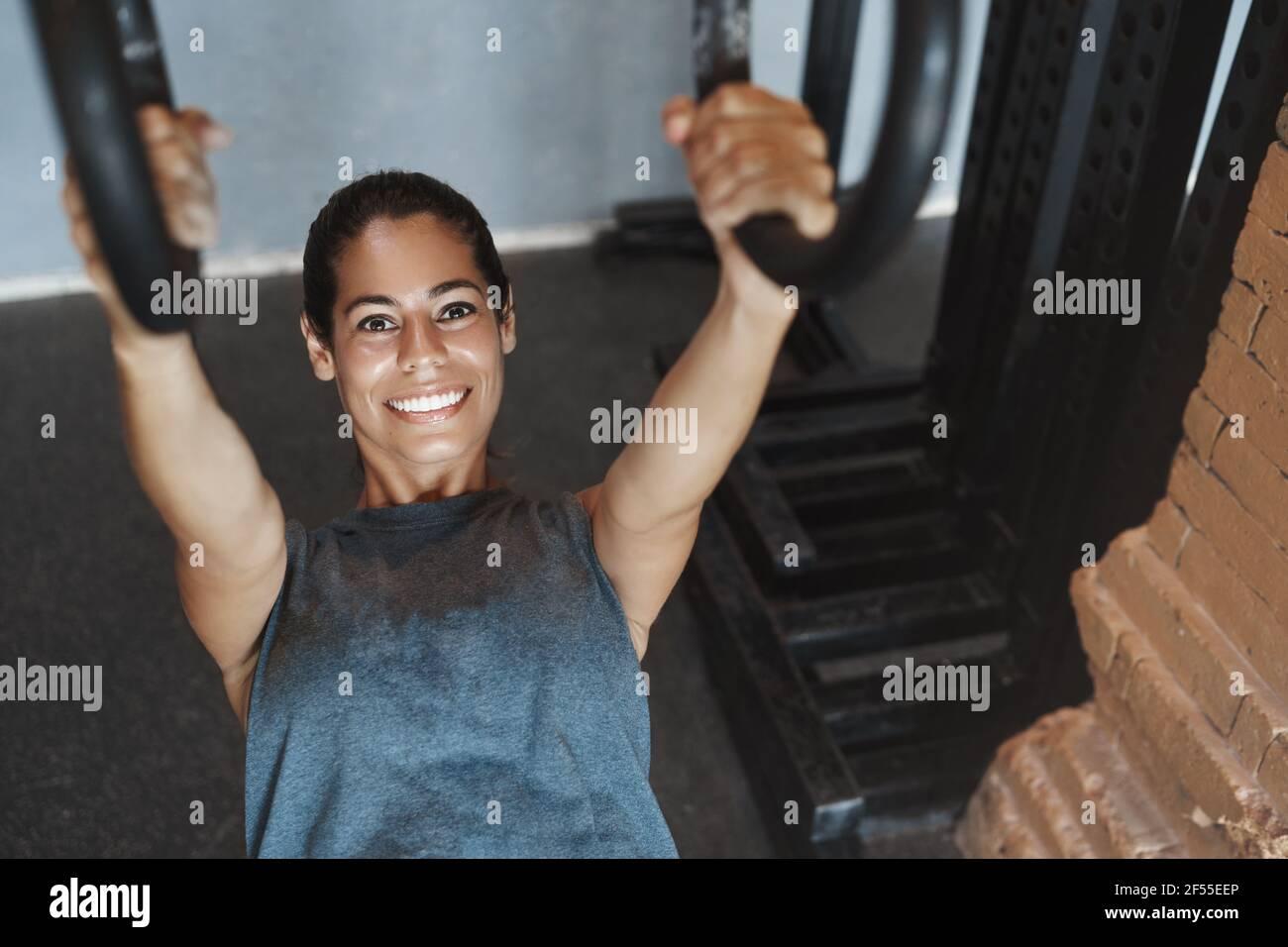 Prise de vue à l'angle supérieur sportswoman sweaty attrayant utilisant l'équipement de gym pour obtenir un ABS parfait, bonne forme du corps, pousser sur les anneaux, pomper les biceps, sourire comme Banque D'Images