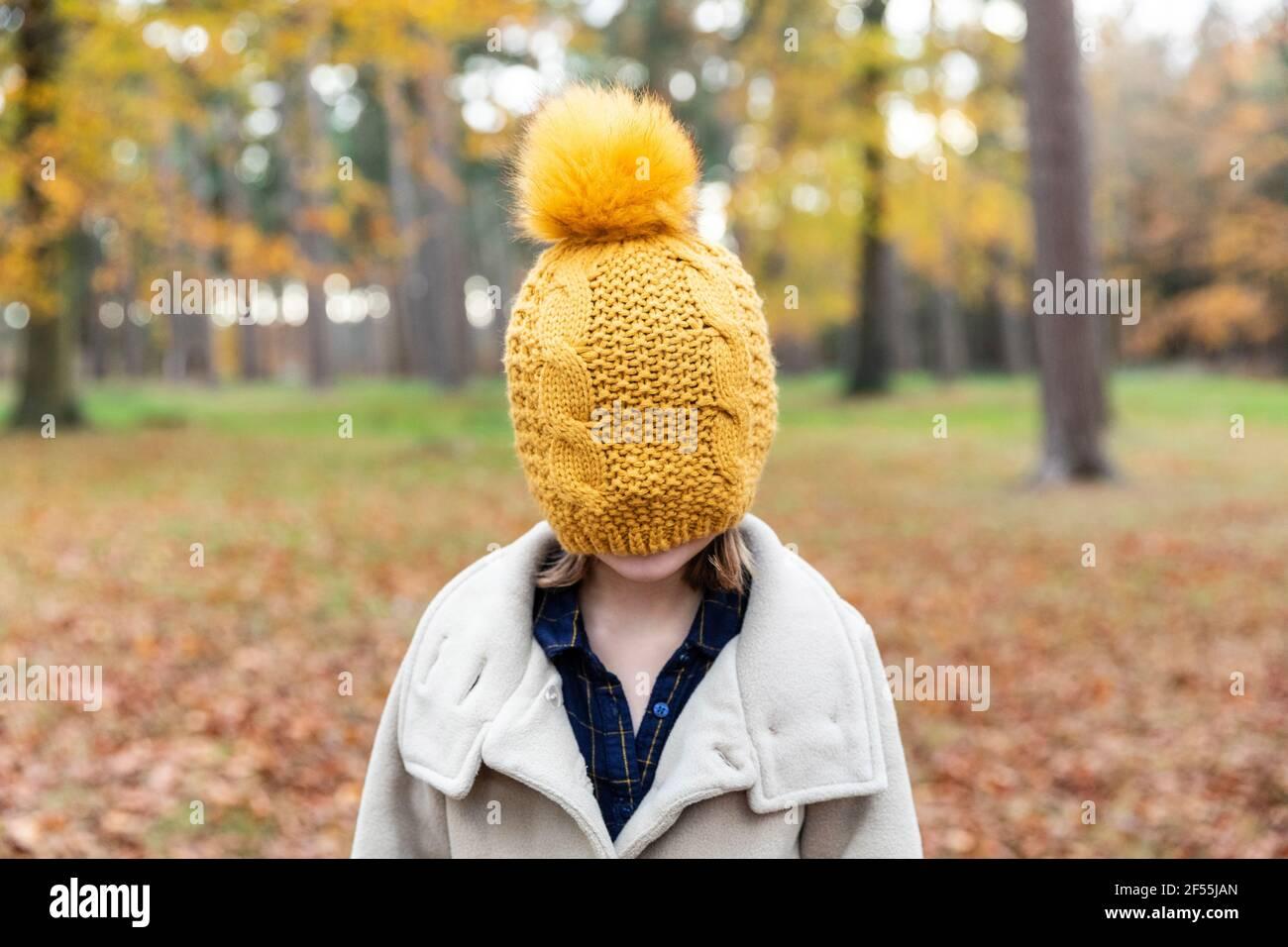 Fille portant une veste couvrant le visage avec un chapeau tricoté pendant qu'elle est debout en forêt Banque D'Images