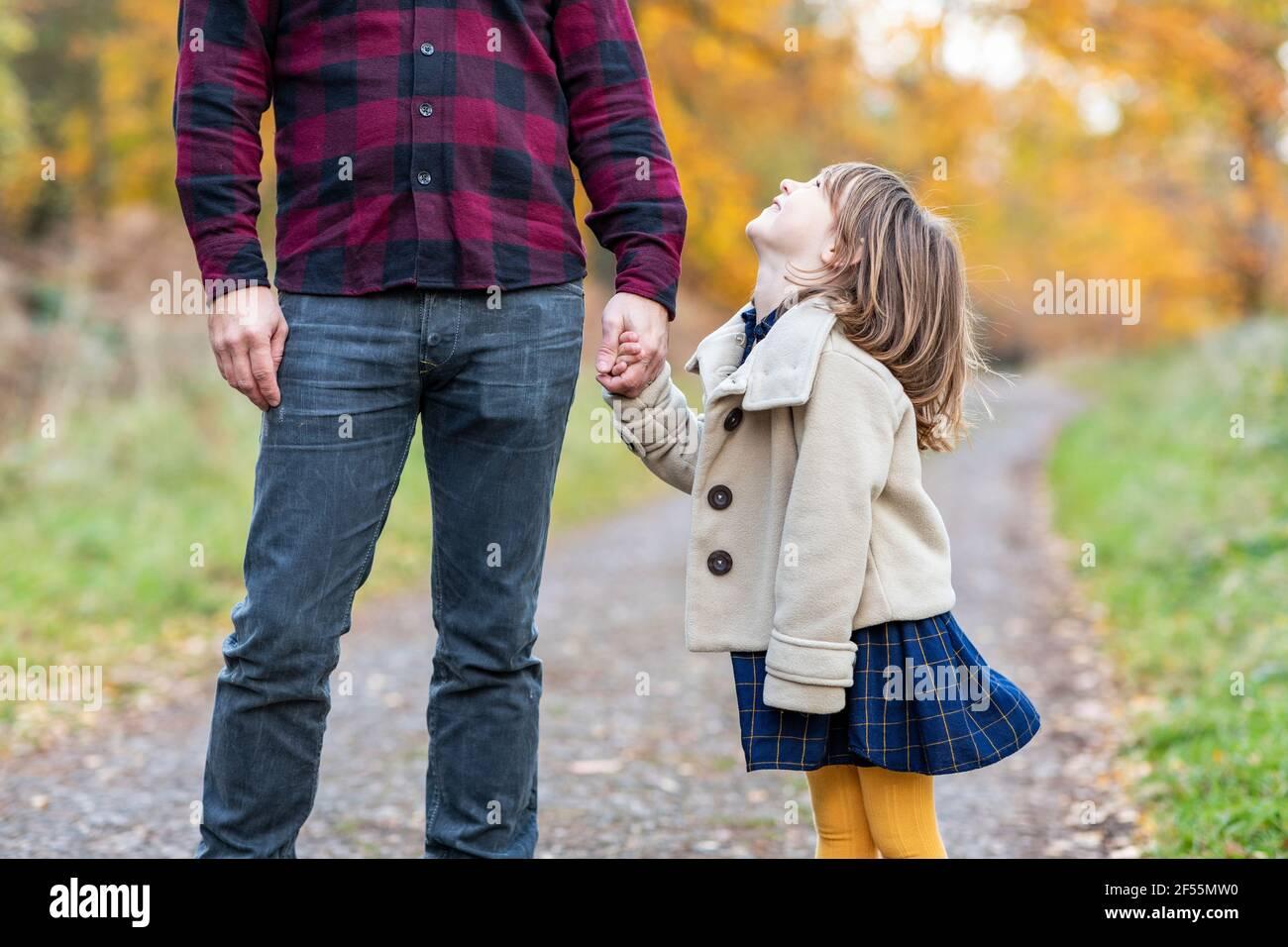 Fille souriante tenant la main du père tout en se tenant debout dans la forêt chemin Banque D'Images