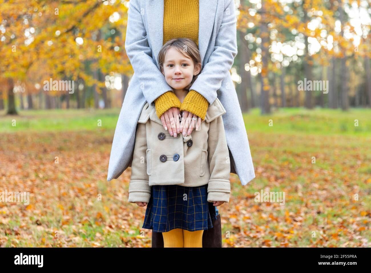 Femme portant une veste debout avec le bras autour de la fille dans la forêt Banque D'Images