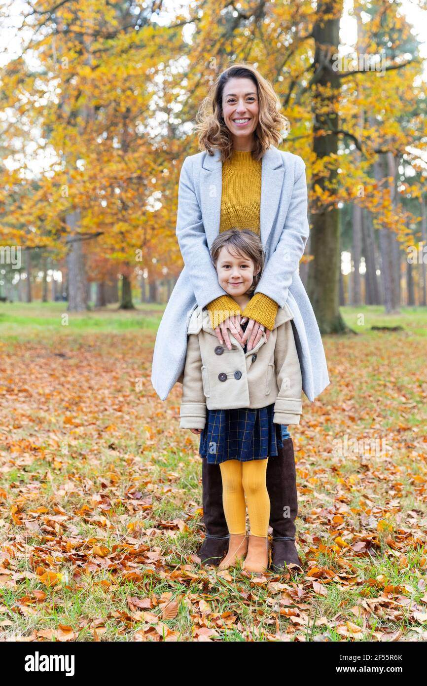 Mère souriante debout avec sa fille en forêt Banque D'Images