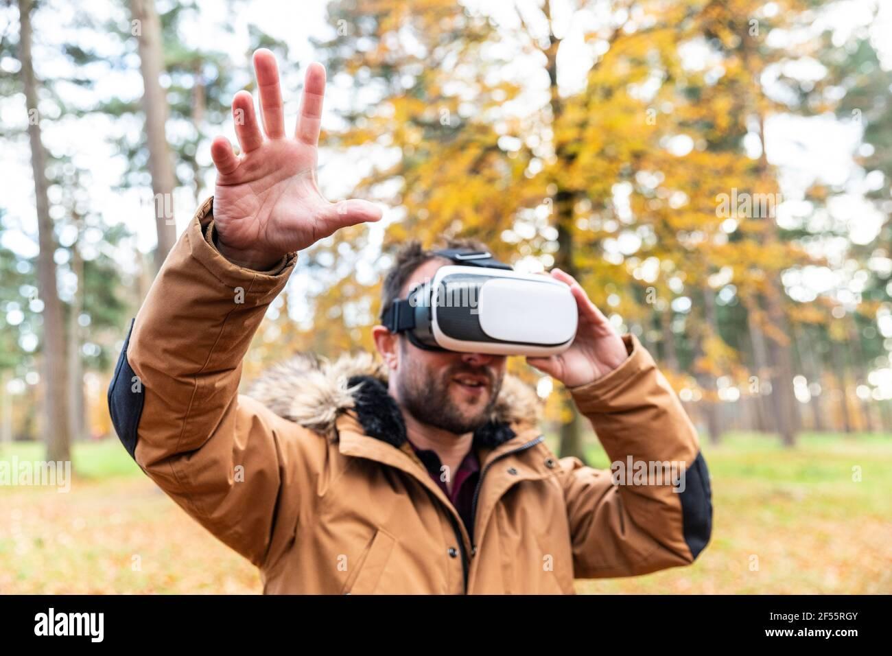 Homme mature utilisant un simulateur de réalité virtuelle en forêt Banque D'Images