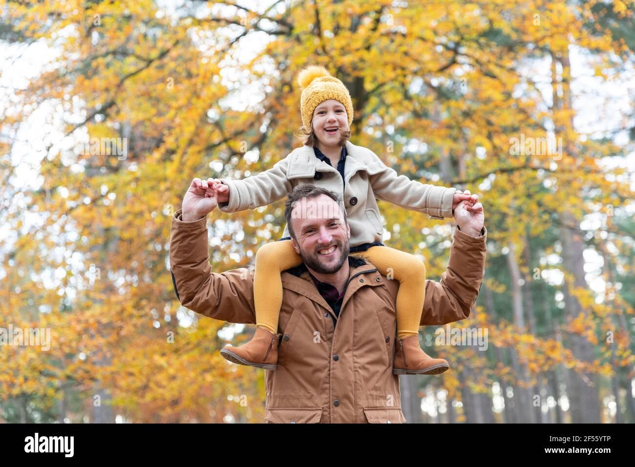 Père joueur portant une fille souriante debout dans la forêt Banque D'Images