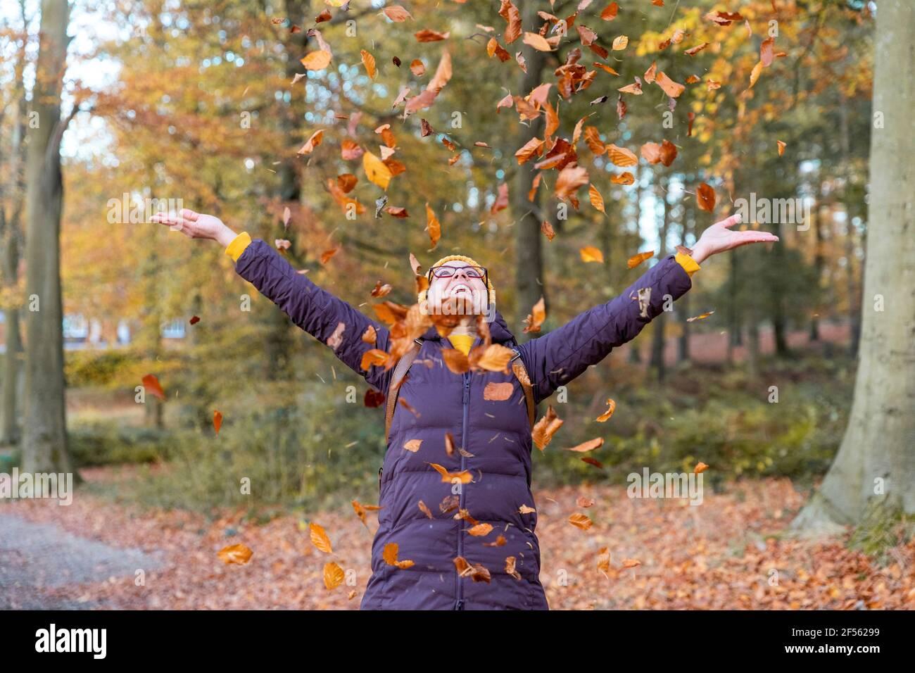 Femme joyeuse jouant avec les feuilles d'automne dans la forêt Banque D'Images