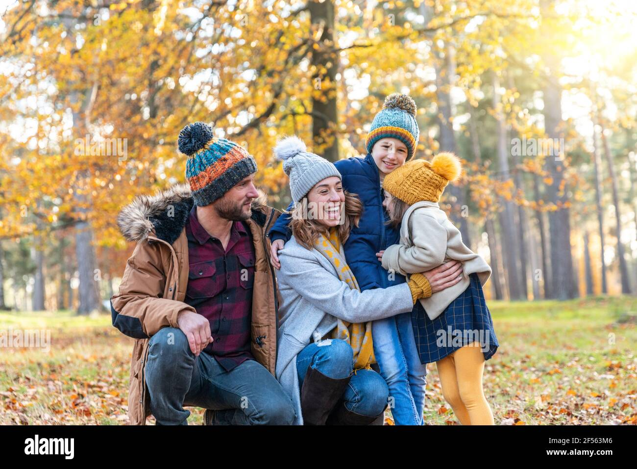 Mère embrassant les enfants tout en croupirant par l'homme dans la forêt Banque D'Images