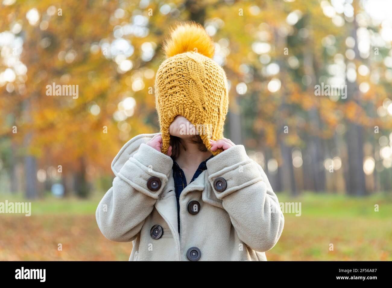 Fille tirant chapeau tricoté tout en jouant dans la forêt Banque D'Images