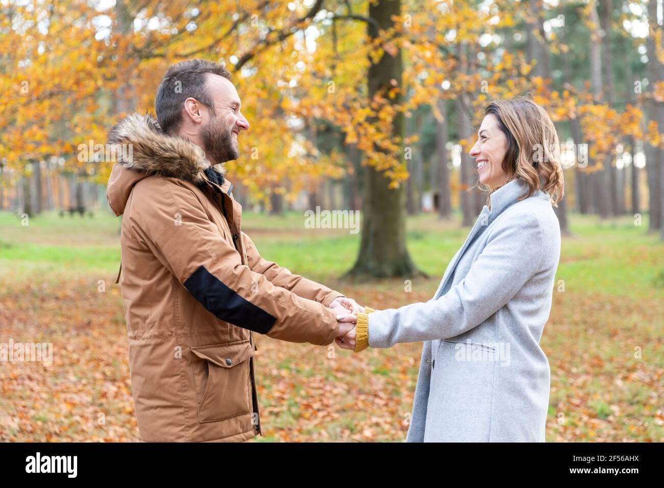 Couple souriant tenant les mains en forêt Banque D'Images