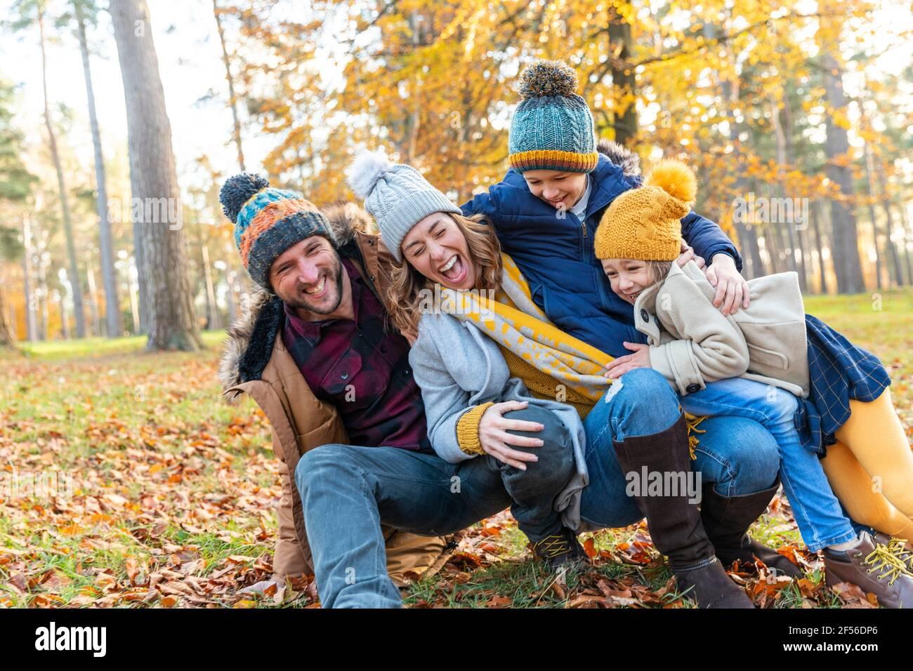 Famille ludique tombant les uns sur les autres tout en s'accroupiant dans la forêt Banque D'Images